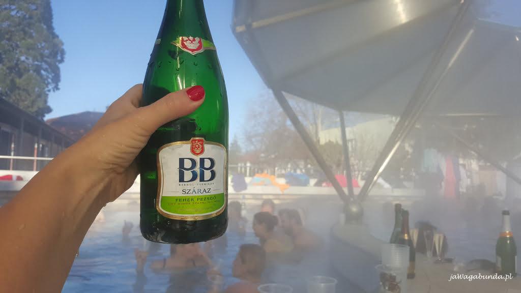 butelka szampana na tle basenu z gorącą wodą