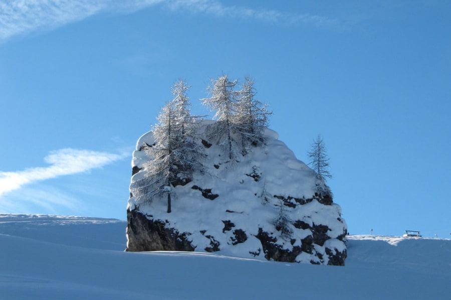 potężny kamień na środku stoku zasypany śniegiem