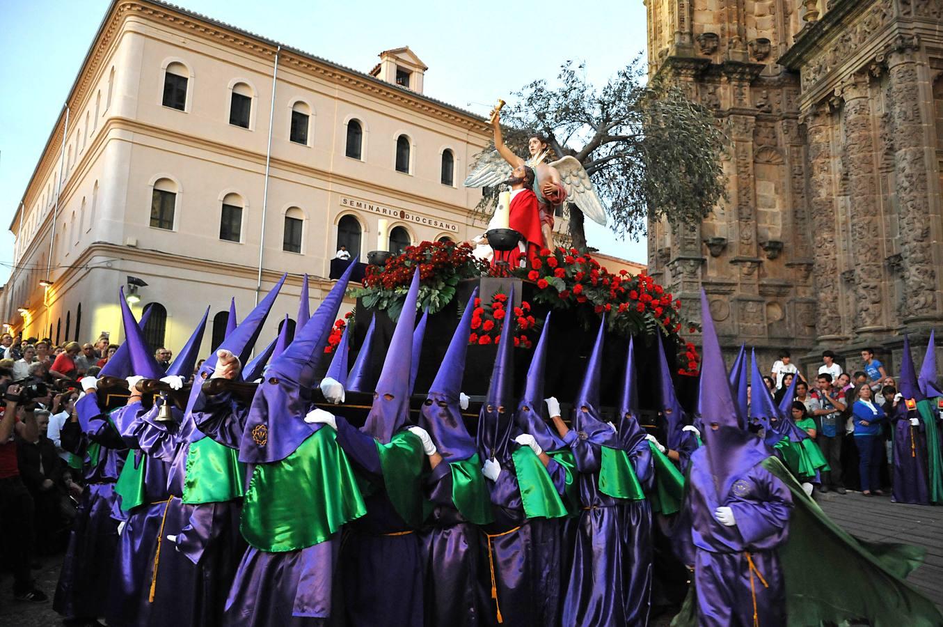 osoby w fioletowych kapturach na głowie niosą na barkach platformę z Chrystusem