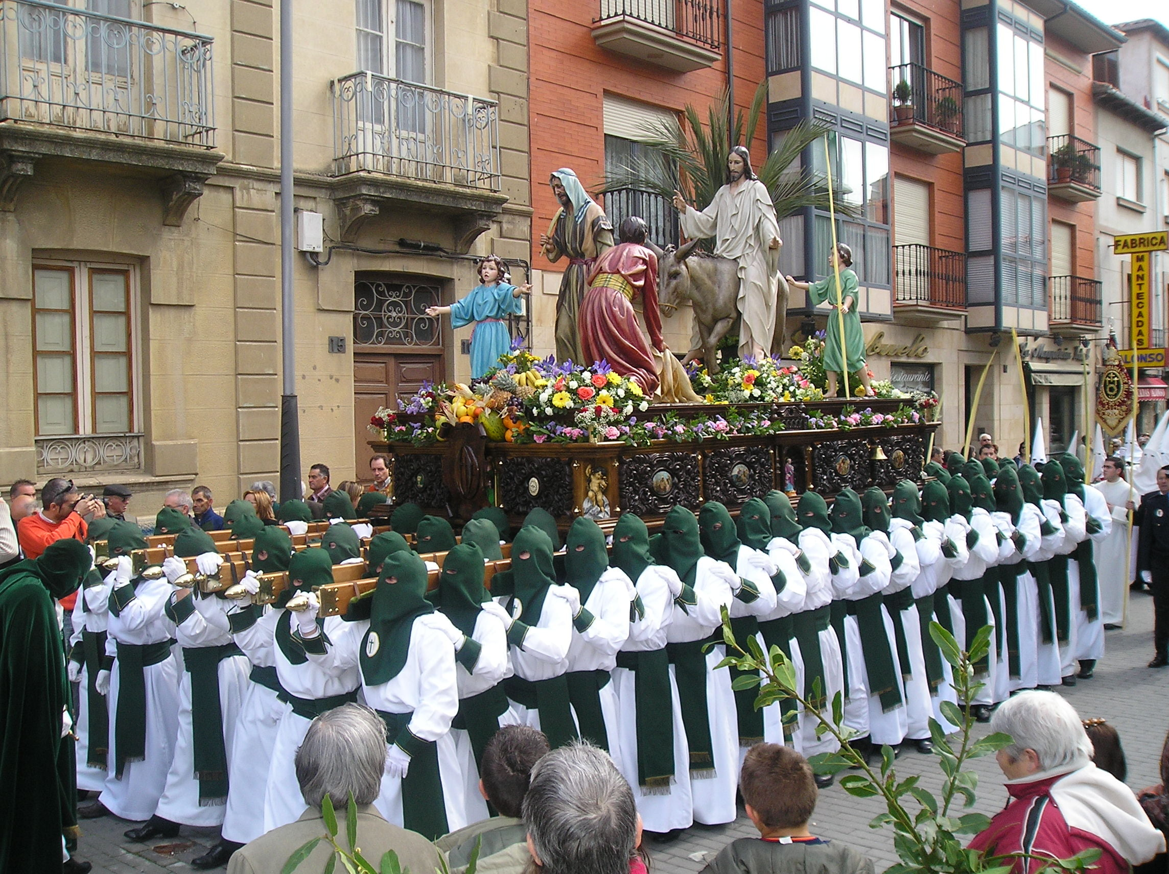mężczyźni niosą na barkach potężną platformę z figurami świętych