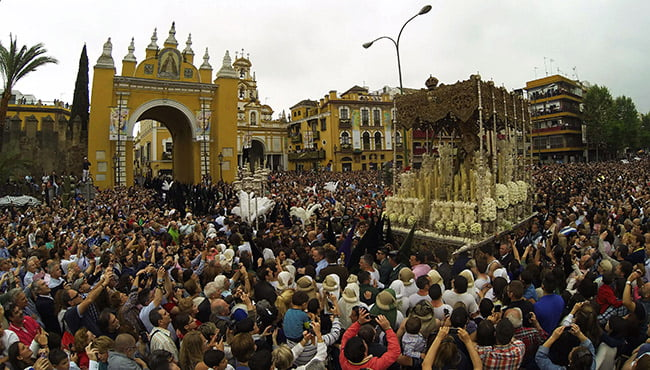 tłum ludzi, dwa kościoły i platforma z rzeźbami świętych