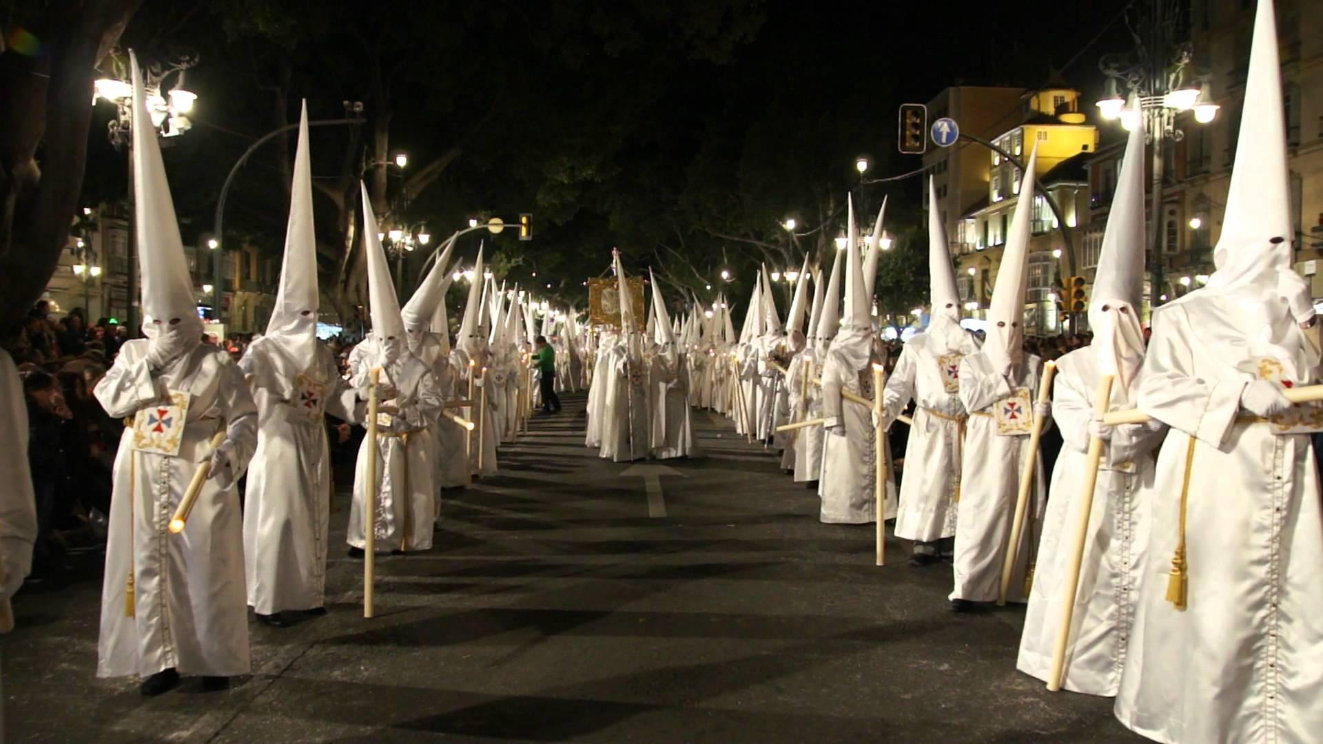 mężczyźni w białych szatach i kapturach zakrywających cała głowę z wyjątkeim oczu
