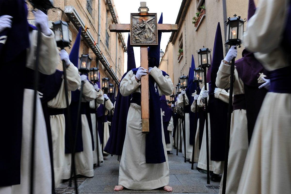 mężczyzna w długiej do ziemi szacie, z kapturem na głowie- boso z krzyżem w dłoni