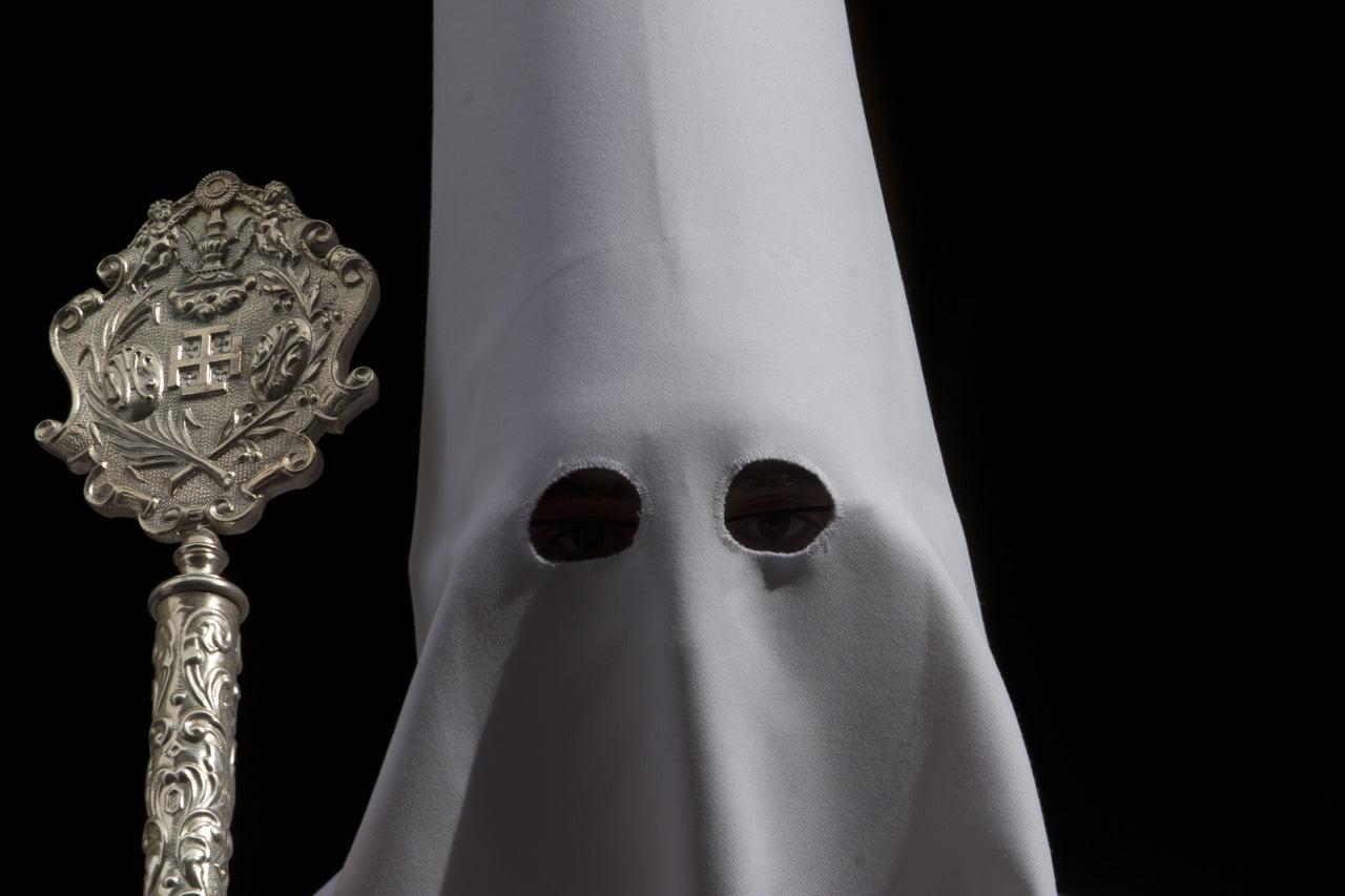 głowa człowieka z kapturem na głowie, tylko z otworami na oczy, widoczne także srebrne berło