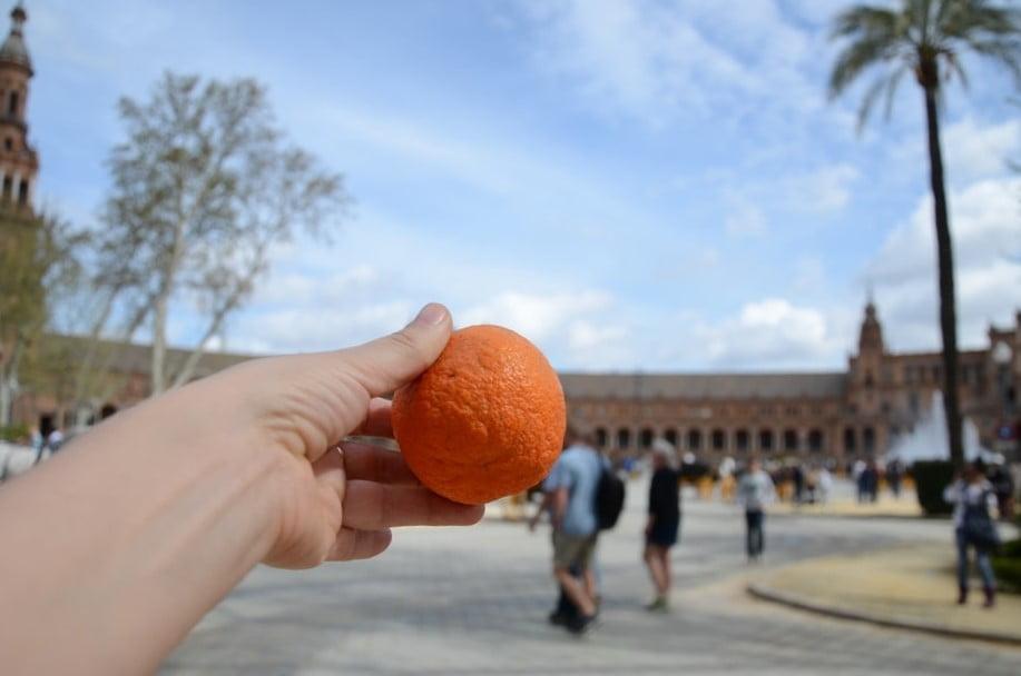 pomarańcza w ręce w tle miasto