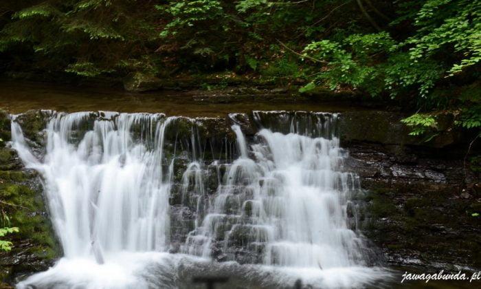 woda spwajaca po kamieniach tworząca wodospad na górskiej rzece