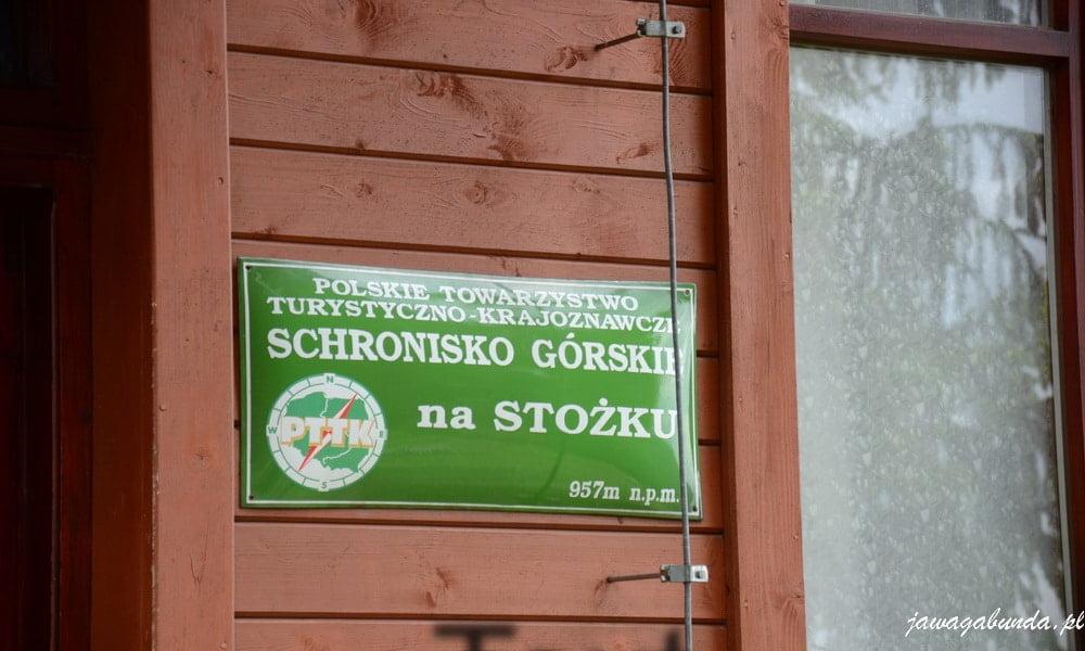 zielona tablica z napisem Schronisko PTTkna Stożku