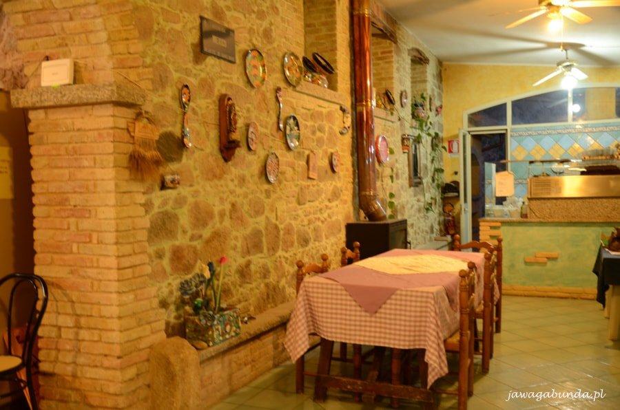 stół nakryty obrusem w kratkę na tle ściany z cegły