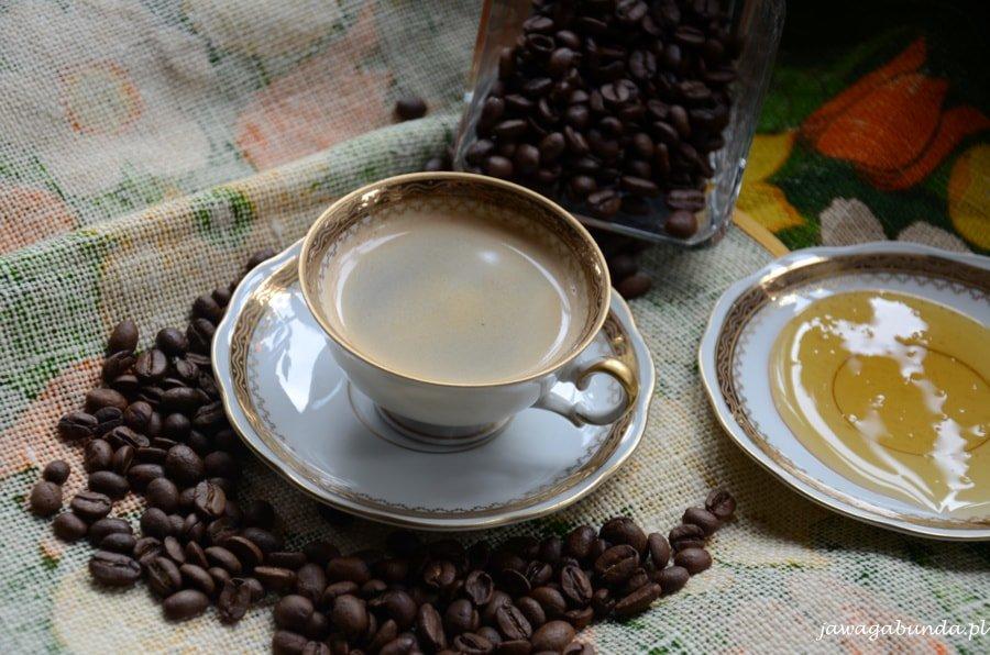 filiżanka kawy, rozsypane ziarna czarnej kawy, miód na talerzyku