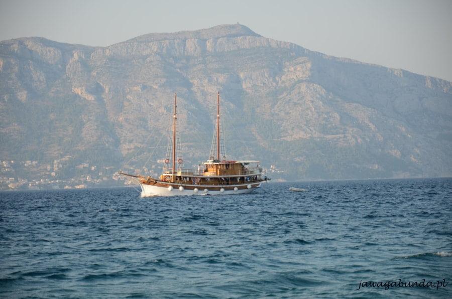 statek płynący na morzu na tle gór