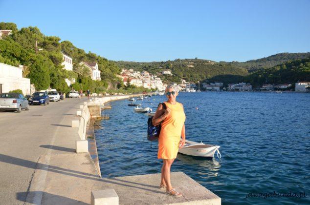 kobieta w pomarańczowej sukience nad morzem