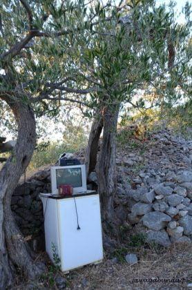 stara pralka a na niej telewizor w tle kamienne murki