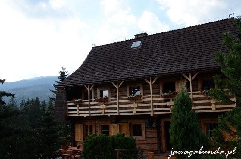 drewnina chata otoczona balkonem, za nią na horyzoncie widoczny szczyt Babiej Góry