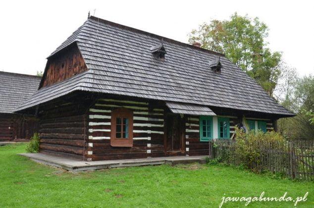 drewniana chata z małymi okienkami, zbudowana z bali. Przy oknach pomalowana na niebiesko.