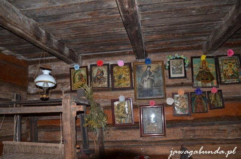Sciana w starej chacie a na niej zawieszone obrazki ze świętmi