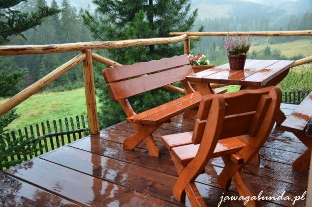 drewniany stół i krzesła na tarasie mokre od deszczu