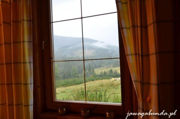 okna a za nim widok na góry z których schodzi mgła
