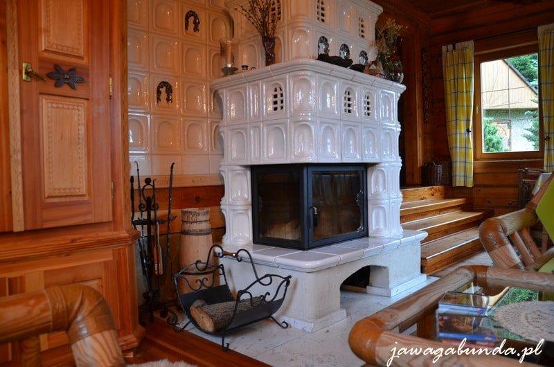 wnętrze drewnianej chaty :piec z białych kafli