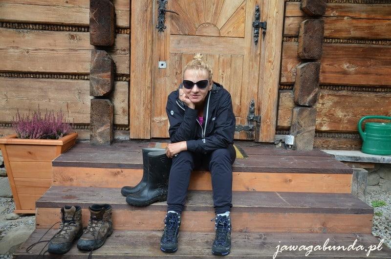 kobieta siedząca na schodach przed drewnianym domem