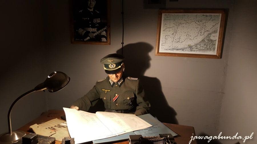 postać niemieckiego oficera przy biurku czyta mapy