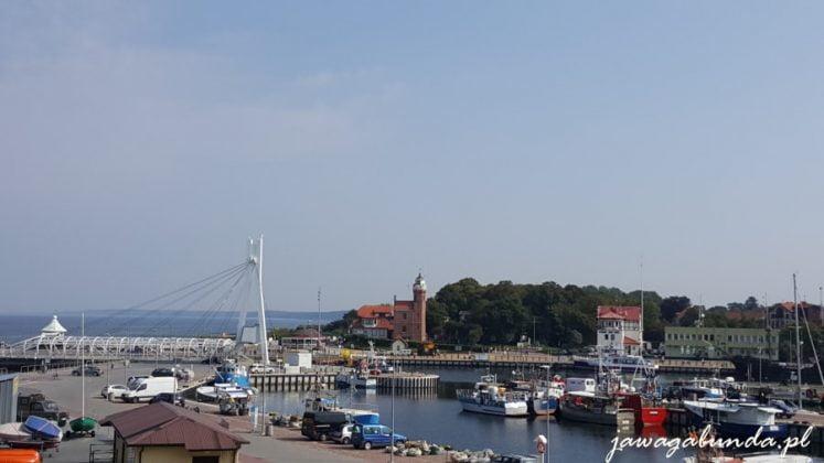 port z jachtami i kutrami rybackimi, w tle latarnia morska