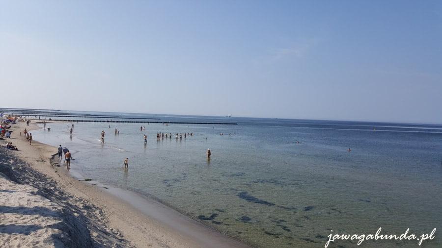 plaża i ludzie chodzący po morzu. Morze gładkie, bez jednej fali