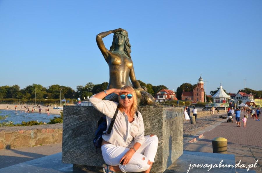 pomnik syrenki morskiej patrzącej w dal i kobieta w takiej samej pozycji
