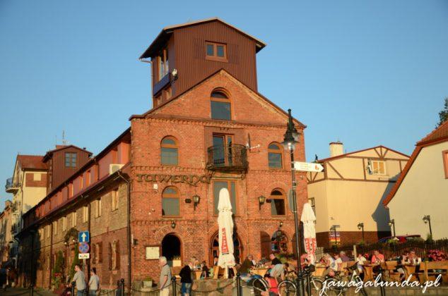 budynek z czerwonej cegły, a przed nim stoliki i parasole