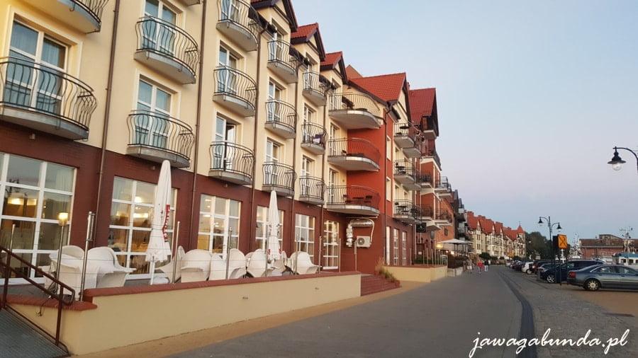 budynek z czerwonej cegły z balkonami, na dole restauracje