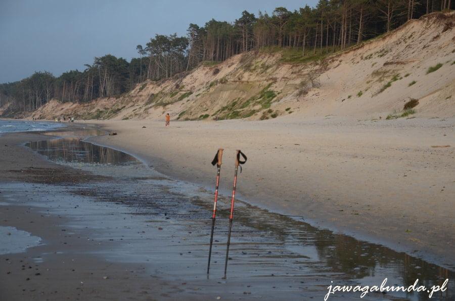 plaża, morze i dwa kije wbite w piach