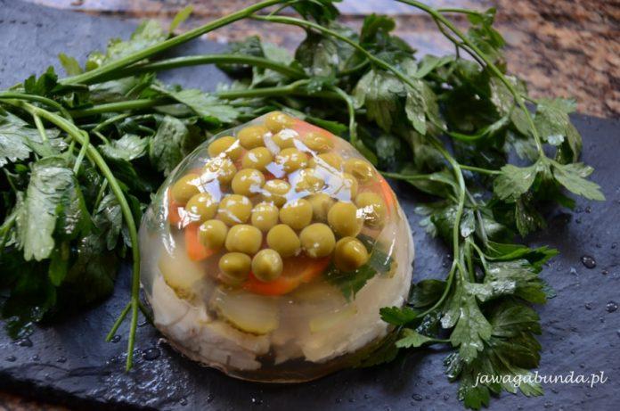 ryba i warzywa w galarecie na czarnej deseczce w otoczeniu zielonej pietruszki