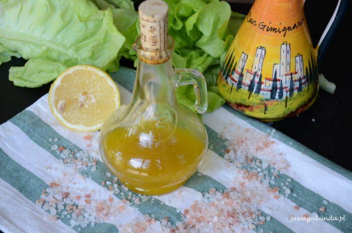 sos z oliwy w przeźroczystym pojemniku wokół rozsypana sól i przekrojona cytryna