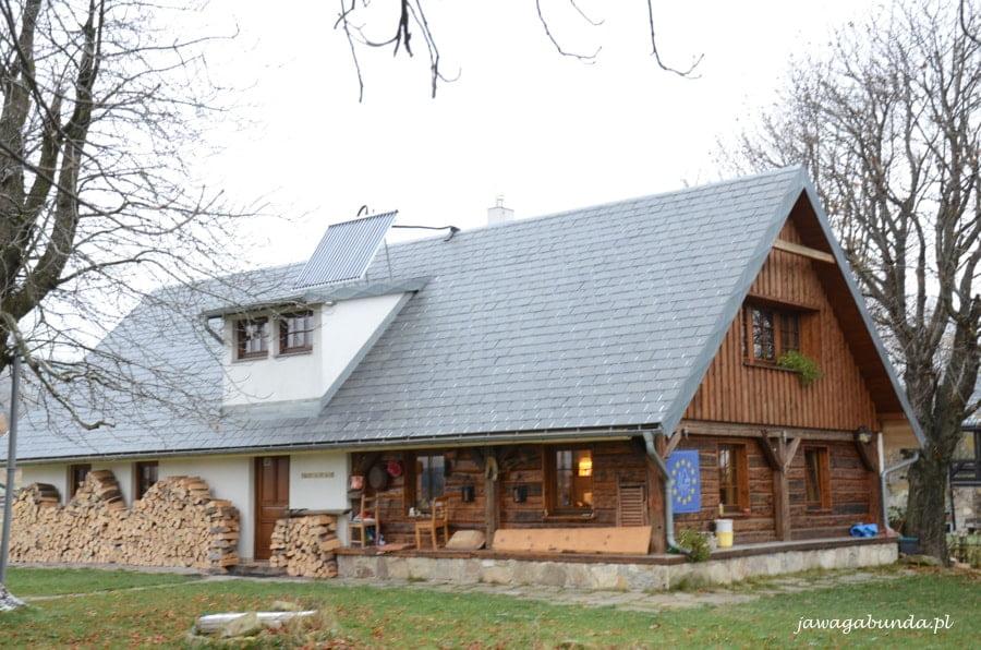 drewniany dom, pod jego dachem skład na drewni