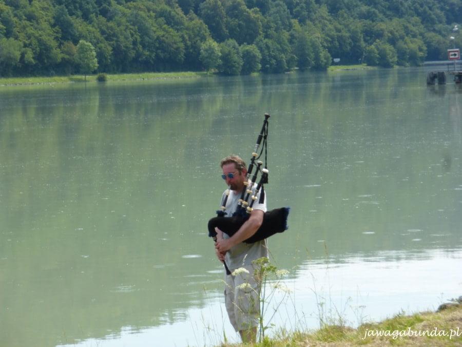 mężczyzna grający na kobzie stoi nad brzegiem rzeki