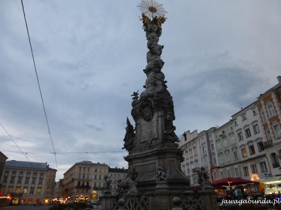 kolumna z rzezbami stojąca na srodku rynku