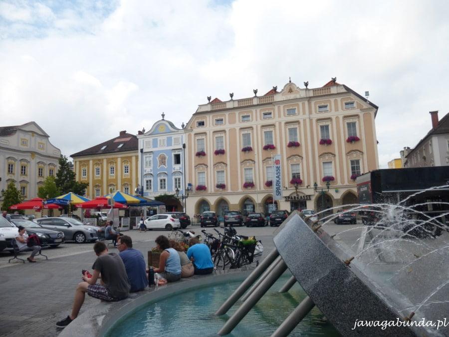 ludzie siedzą na murku fontanny, na rynku wokół kamienice