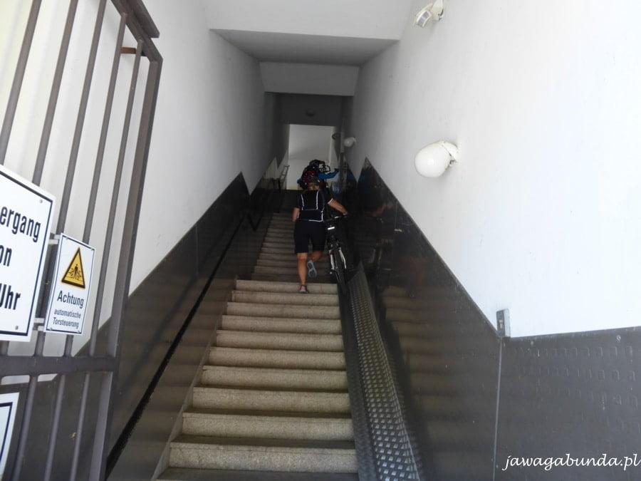 osoba niesie rower po stromych schodach