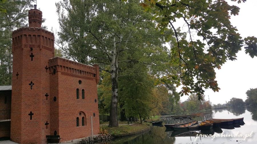 budynek z cegły , obok rzeka a na niej łódki