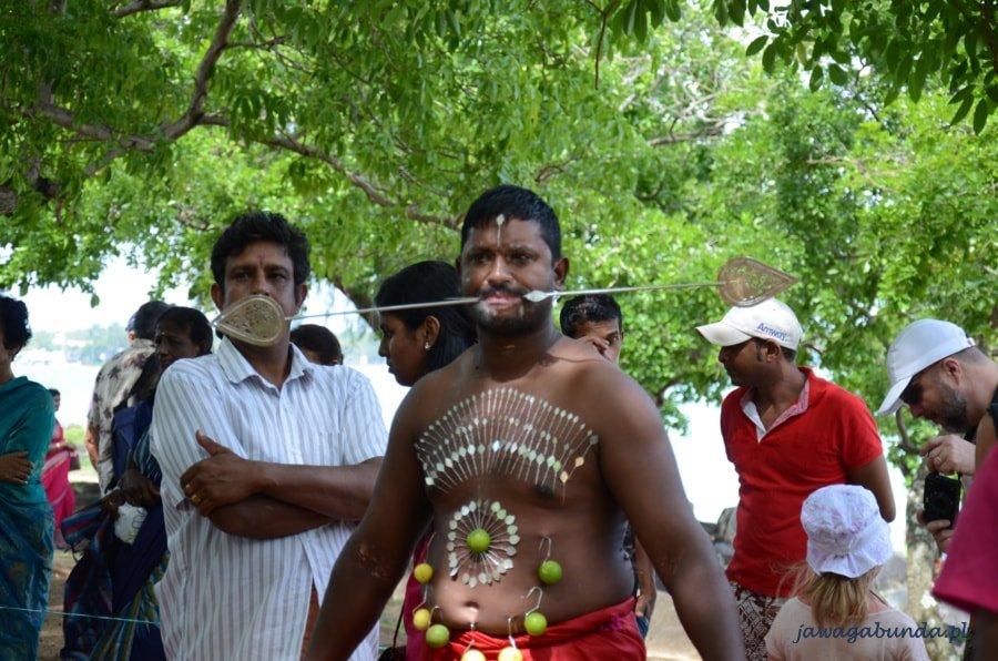 mężczyzna z policzkami przekłutymi małą dzidą i powbijanymi w ciało szpilami