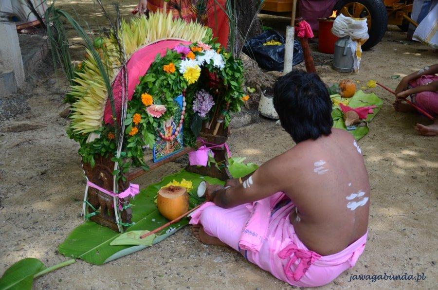 mężczyzna siedzący na ziemi przed kolorowym ołtarzem