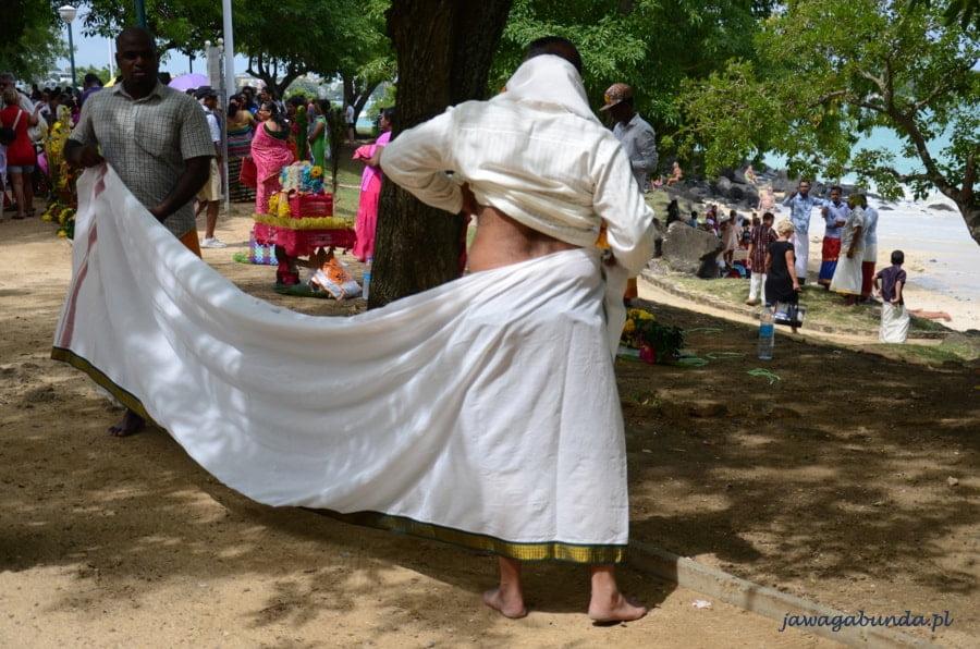 mężczyzna zawijający sobie spódnicę wokół bioder