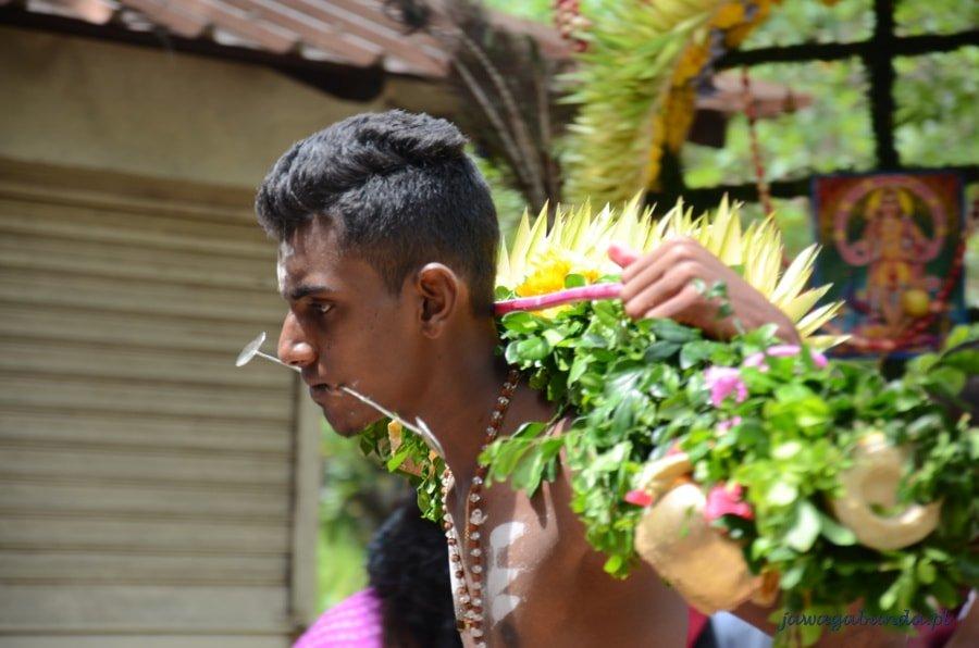 mężczyzna niosący kolorowy kwiatowy ołtarz