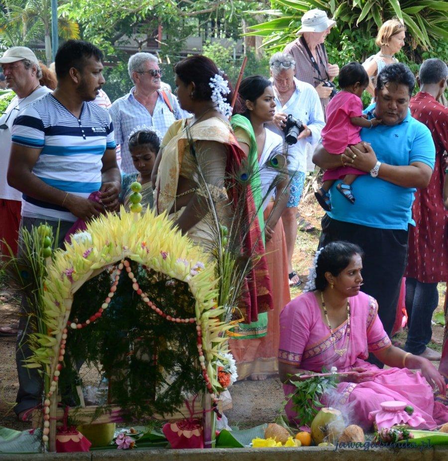 ludzie stojący wokół ołtarza wykonanego z kwiatów