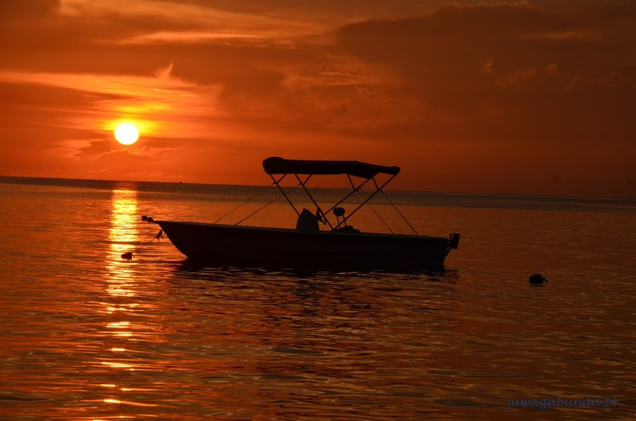 łodka na morzy i zachód słońca
