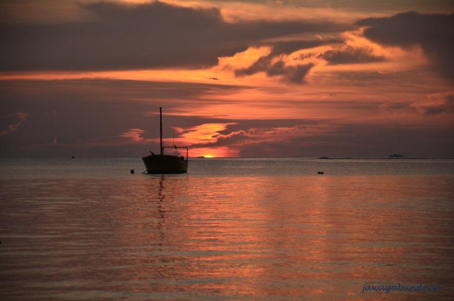 łódka oświetlona zachodzącym słońcem