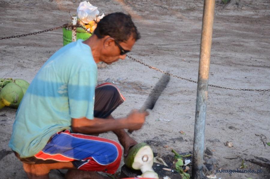 mężczyzna z maczetą otwierający kokos