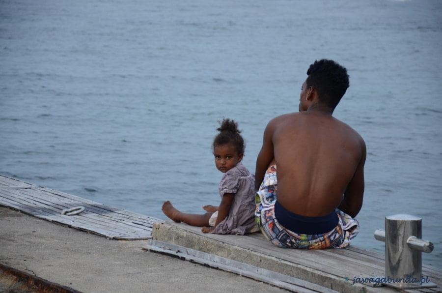 mężczyzna o ciemnej skórze i dziewczynka siedzą na pomoście nad morzem