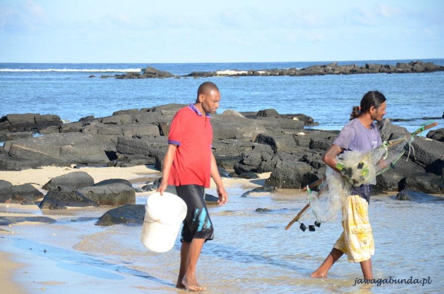 dwóch mężczyzn idących brzegiem morza