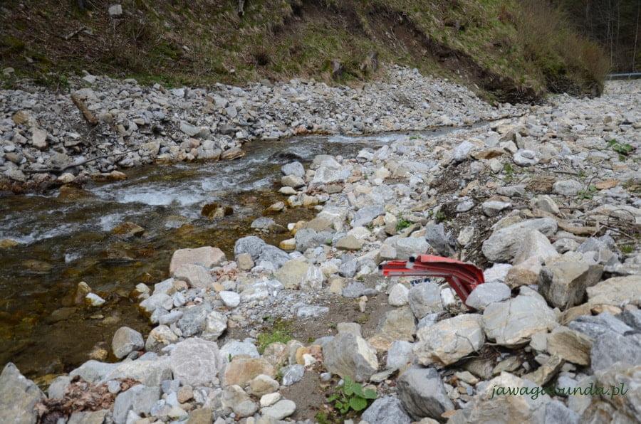 czerwone części zniszczonego samochodu w rzece