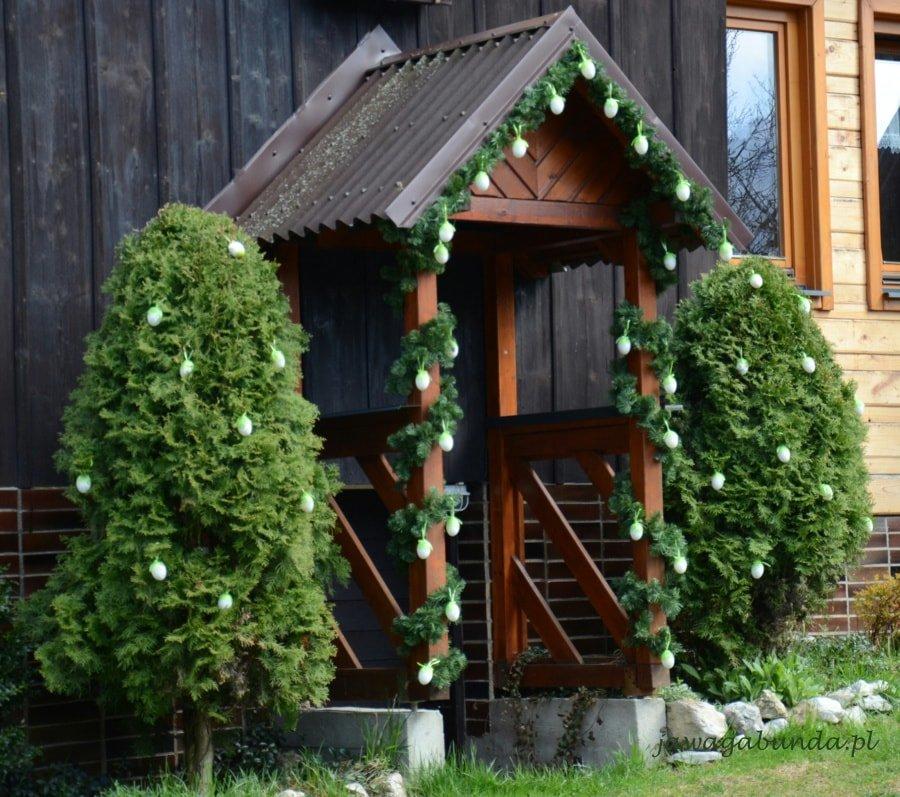 dom przyozdobiony zielonymi gałęziami i kolorowymi jajkami